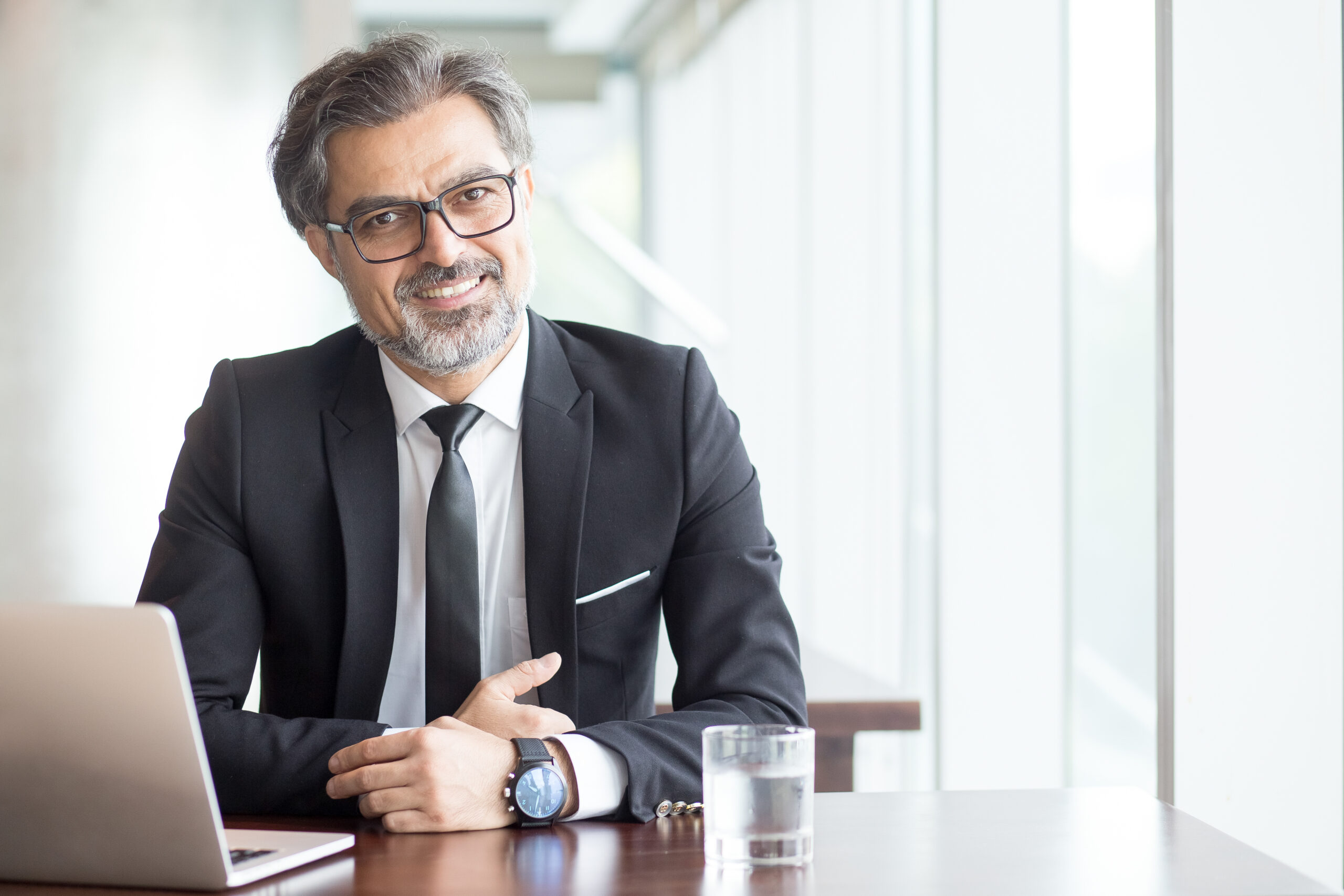 Cheerful businessman in eyeglasses working in office or coworking space. Portrait of confident male executive with gray hair at table. Successful business concept